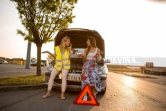 Two beautiful young women are on the road away from town with their broken car. They're waiting for a towing service. The blonde tries to get help over the phone and the brunette has battery cables in her hands.