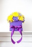 Beautiful decoration of chrysanthemum flowers. The flowers are yellow and purple and are in the handmade box with the bow also purple. Behind is a white background.