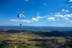 The instructor and tourist are flying high above on a yellow-blue paraglider. The sky is beautiful blue with clouds and below the fields is a small town.