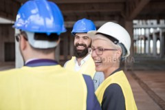 Hipster construction Architect is at a construction site with his team.