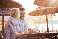 A handsome bearded young man and his pretty blonde girl sit in a restaurant on the seashore and they are happy because they bought something nice on the online shop.