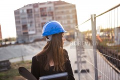 A beautiful young woman inspector checks the building while she is at a construction site.