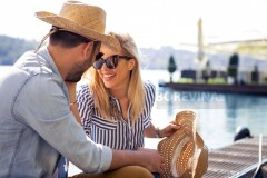 A Beautiful young blond woman spends beautiful moments with a handsome guy on the riverbank.