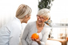 A senior blonde woman explains to a young woman how to live healthy and what to use for nutrition. She laughs and has one orange in her hand.