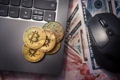 Top view of bitcoin gold coins on laptop and next to US dollar banknotes and computer mouse