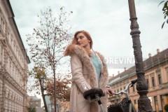 A beautiful redhead in a fur coat with her bike