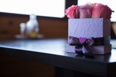 Box with beautiful pink roses on the table.