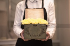 A decorative box full of yellow flowers.