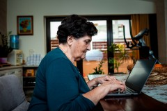 An elderly senior lady sits at a dining table and uses a computer. She looks at something on the Internet and intends to order some things through the online store