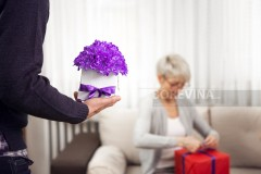 Handsome young man brings a beautiful purple flowers to his mother who in her arms hold another gift.